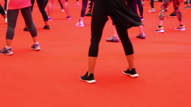 low section view group of women dancing during exercise class on red floor - exercise class stock videos & royalty-free footage