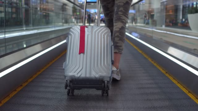 low sections of a young woman walking in a moving walkway in airport - kamerafahrt auf schienen stock-videos und b-roll-filmmaterial