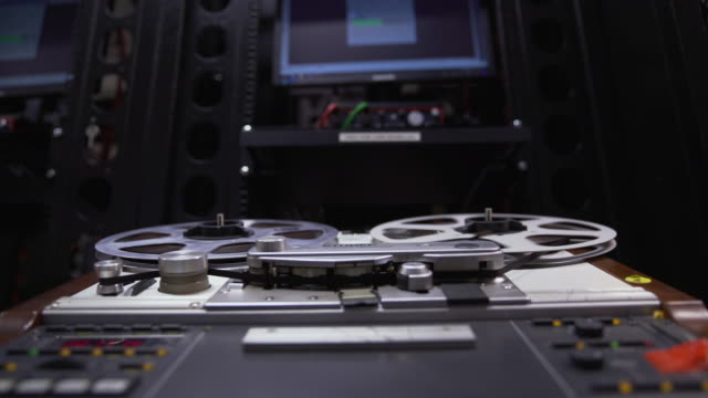 Low shot of a 'Struder' reel to reel film player with a computer terminal in the background