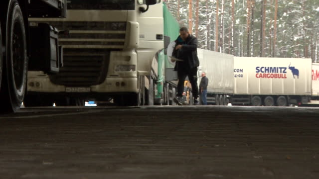 Low shot of driver exiting lorry at Lithuanian/Belarus border with snowy background