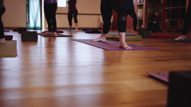 low, schiebe-schuss von yoga-kurs - sich verschönern stock-videos und b-roll-filmmaterial