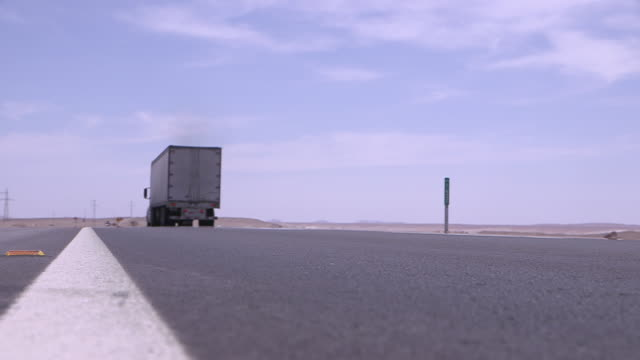 low, static shot of a white lorry driving away along an empty, modern road, chile. - lastzug stock-videos und b-roll-filmmaterial