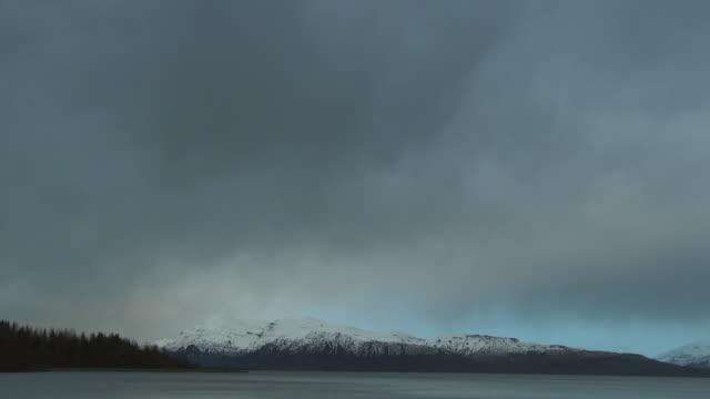 vídeos de stock e filmes b-roll de low storm clouds drift over a wooded coast in alaska. - alasca