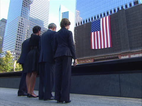 vidéos et rushes de low sweeping shot of president obama, president bush, and their wives bowing their heads at the 9-11 memorial on the morning of 9/11/11, the tenth... - mémorial