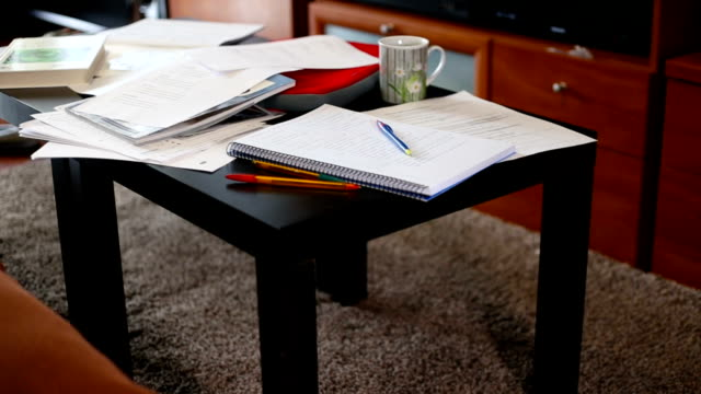 low table in the living room covered with books and study notes - desk stock videos & royalty-free footage
