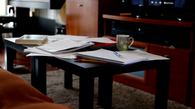 vídeos de stock e filmes b-roll de low table in the living room covered with books and study notes - caos