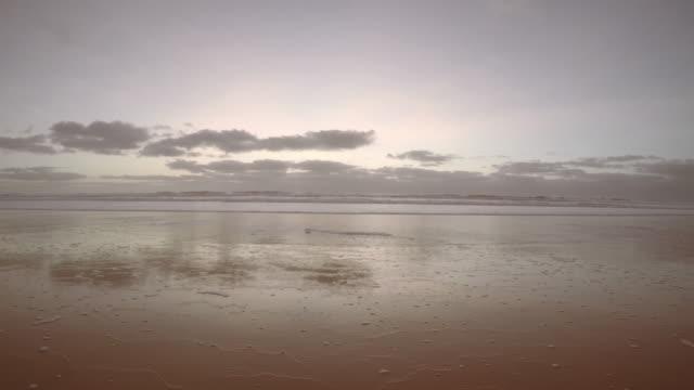 vídeos de stock, filmes e b-roll de maré baixa na praia ao pôr do sol - vazante