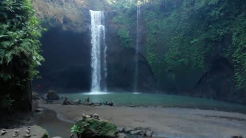 stockvideo's en b-roll-footage met lage tot hoge schot van watervallen in een dichte jungle - bali