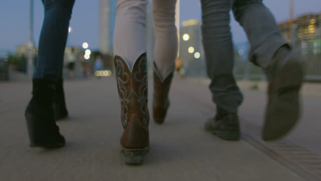 stockvideo's en b-roll-footage met low tracking shot of friends' feet walking across pedestrian bridge at night - austin texas