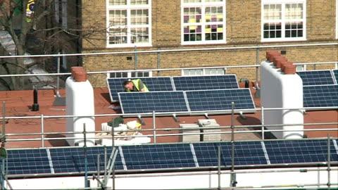 low uptake of solar panel installations in london; t01041234 / brixton: loughborough estate: **jaffa interview overlaid sot** solar panels on roof of... - ジャファ点の映像素材/bロール