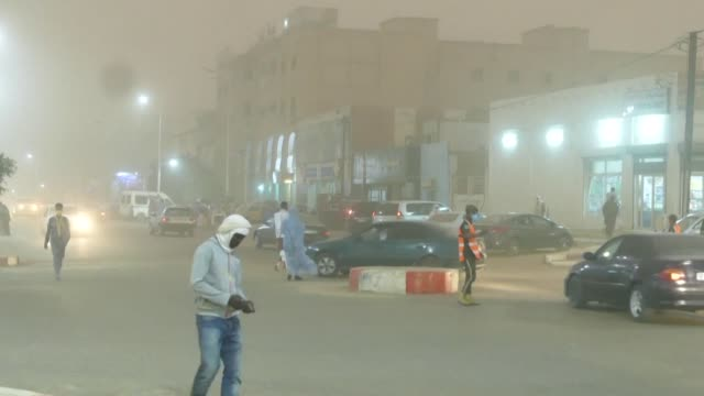 low visibility cars with fog lights on and ghostly silhouettes in almost deserted streets: mauritania's capital nouakchott was covered on monday by a... - nouakchott stock videos & royalty-free footage