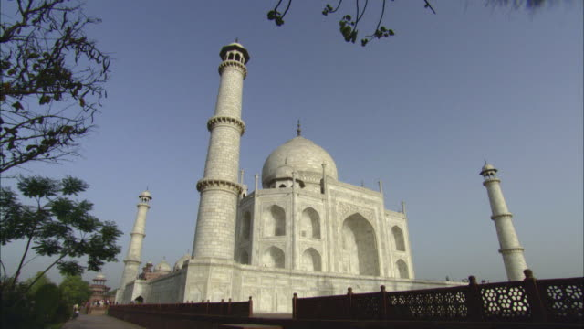 la ws pan low wall surrounding taj mahal under clear blue sky / agra, india - surrounding stock videos and b-roll footage