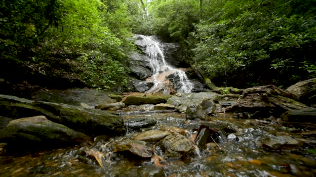 low wide angle shot up creek towards waterfall - quarzo video stock e b–roll