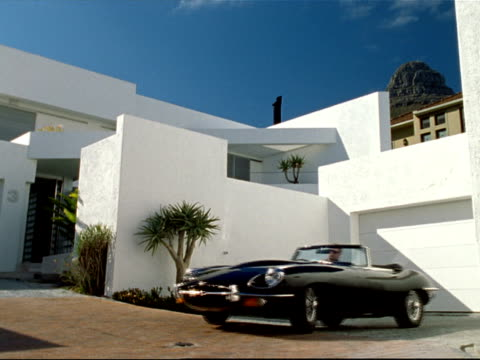 low wide angle view man pulling convertible black jaguar e-type out of driveway of modern house - ein mann allein stock-videos und b-roll-filmmaterial