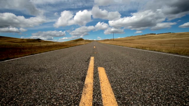 vidéos et rushes de low wide angle view of empty paved road with puffy clouds and blue sky with shadows rolling across landscape. - low angle view