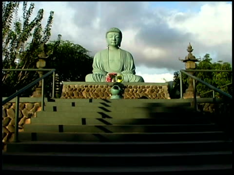 low wide shot looking up stairs to a buddha statue. - female likeness stock videos & royalty-free footage