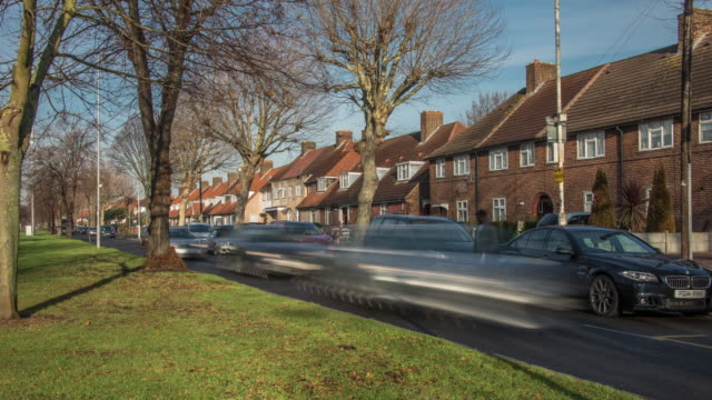 a low winter sun casts shadows across the small green as local traffic moves past suburban housing and parked cars in east london - stationary stock videos & royalty-free footage