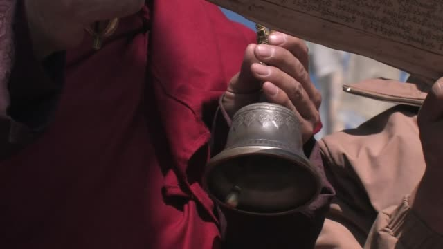 low-angle close-up of a buddhist monk ringing a bell and chanting a prayer. - chanting stock videos & royalty-free footage