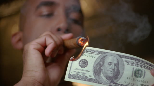 low-angle close-up of man lighting cigar with us$100 bill / exhaling smoke - showing off stock videos & royalty-free footage