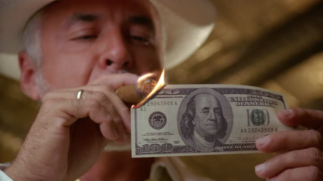 low-angle close-up of man with white beard lighting cigar with us$100 bill - greed stock videos and b-roll footage