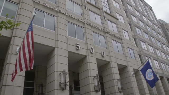 Low-angle establishing shot of US Immigration and Customs Enforcement building in DC