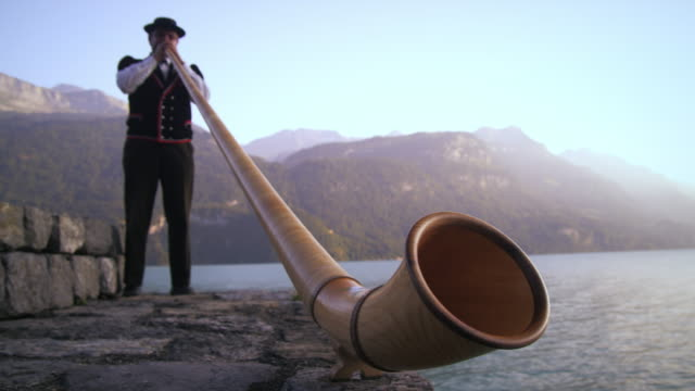 low-angle footage of man playing alphorn next to lake - solo uomini maturi video stock e b–roll