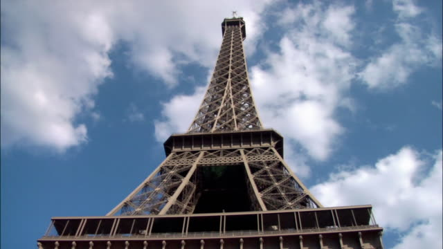 low-angle lockdown looking up at eiffel tower as clouds drift by overhead / paris, france - untersicht stock-videos und b-roll-filmmaterial
