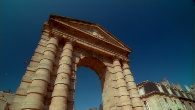 low-angle lockdown of flock of birds flying from columns to architrave of porte dijeaux at place gambetta in bordeaux, france - architrav stock-videos und b-roll-filmmaterial