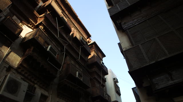 low-angle pan-left of wooden latticed windows and balconies in the historic centre of jeddah. - jiddah点の映像素材/bロール