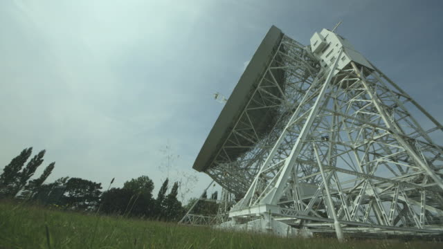 Low-angle real-time shot showing the slow movement of the enormous Lovell Telescope radio dish at the Jodrell Bank Observatory in Cheshire, UK.