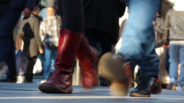 low-angle sequence showing people's feet as they walk on a busy pavement on a high street in london, uk. - ora di punta video stock e b–roll