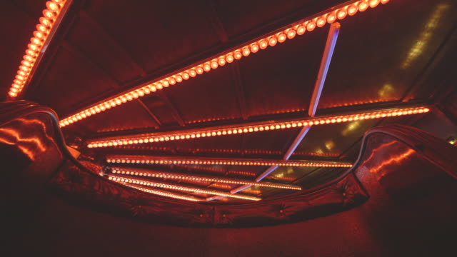 Low-angle sequence taken from the foot of a waltzer car of fanning lines of red bulbs flashing on and off in patterns at a fairground in the UK.