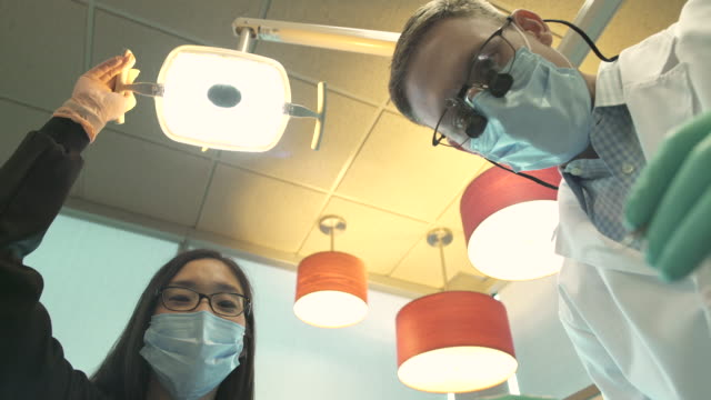 stockvideo's en b-roll-footage met low-angle shot of a dentist at work - elektrische lamp