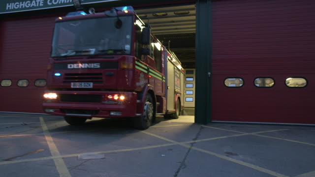vídeos de stock e filmes b-roll de low-angle shot of a fire engine leaving a fire station with its emergency lights on at dusk, uk. - carro de bombeiro