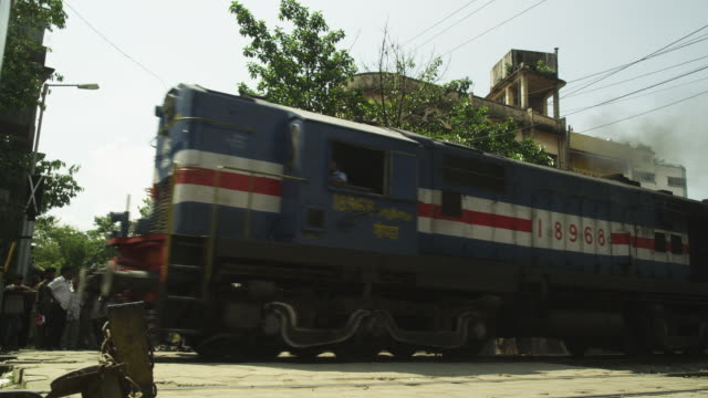 Low-angle shot of a freight train as it passes a level crossing in Guwahati in Assam, India.