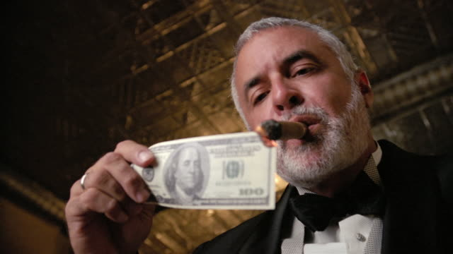 vídeos de stock, filmes e b-roll de low-angle shot of man in tuxedo lighting cigar with us$100 bill - riqueza