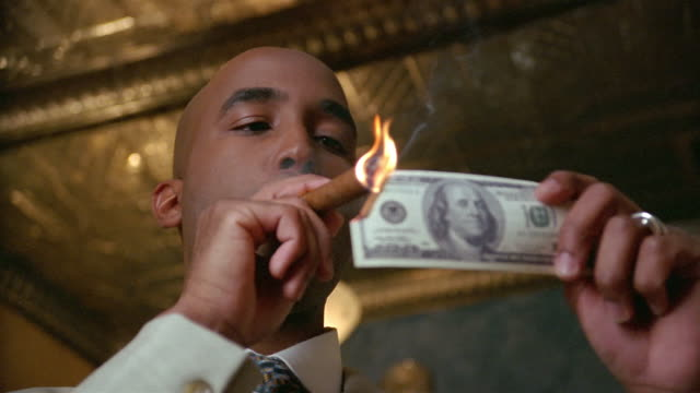 low-angle shot of man lighting cigar with us$100 bill - greed stock videos and b-roll footage