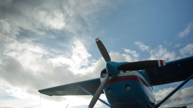low-angle shot of small plane with moving clouds - プロペラ機点の映像素材/bロール