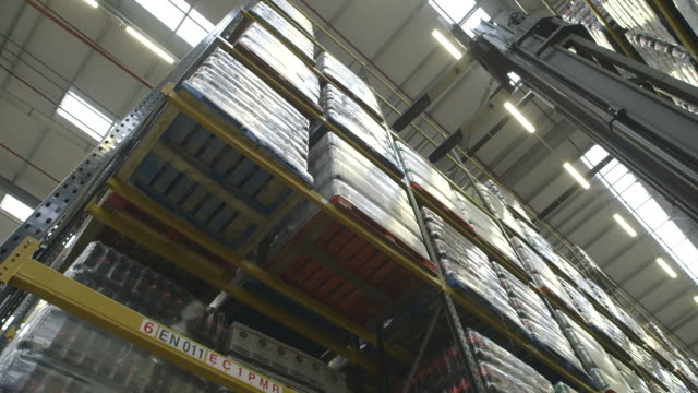 Low-angle shot showing a forklift vehicle picking up, bringing down, then replacing a pallet loaded with bottles, UK.