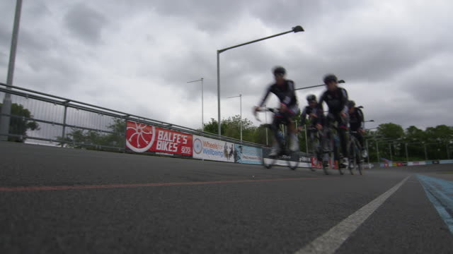 low-angle, static shot of a group of four male cyclists wearing elastane clothing approaching the camera at a velodrome in the uk. - lycra stock-videos und b-roll-filmmaterial