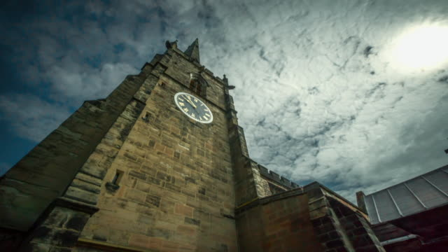 Low-angle time-lapse showing the movement of the hands on a clock face on the tower of an old church against a moody sky, Nottinghamshire, UK.