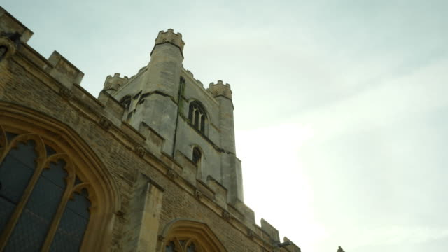 Low-angle tracking shot showing the sun shining from behind the University Church of St Mary the Great, Cambridge, UK.