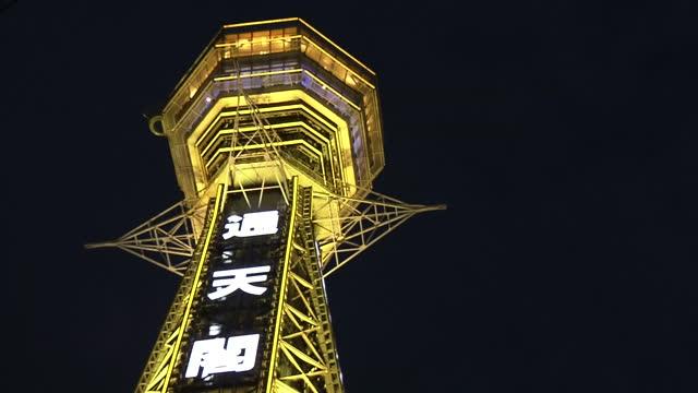 low-angle, cu, tsutenkaku tower lit up in yellow, osaka, japan - local landmark stock videos & royalty-free footage