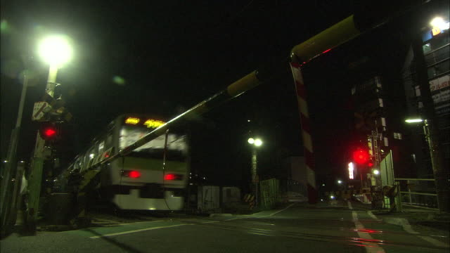 vídeos y material grabado en eventos de stock de low-angle view; a train passing the railway crossing on the yamanote line at night; the crossing bars getting up after the train was gone; the... - equipo de seguridad
