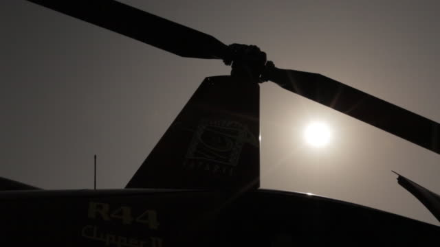 low-angle view of a helicopter's blades as the aircraft starts up against bright sushine. - hubschrauber stock-videos und b-roll-filmmaterial