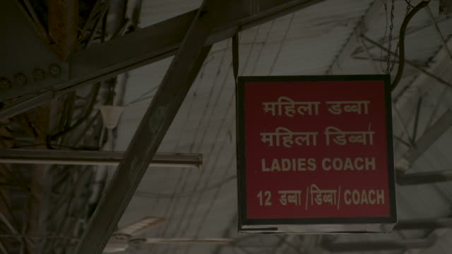 low-angle view of a sign indicating where a ladies' carriage will stop on commuter train, mumbai, maharashtra, india. - 言語翻訳点の映像素材/bロール