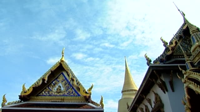 low-angle view of the phra sri rattana chedi spire, and ornate rooftops with golden prangs. - spire stock videos & royalty-free footage