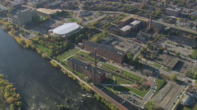 aerial lowell historic park, merrimack river, sports arena, and small city along the riverbank / lowell, massachusetts, united states - industrial revolution stock videos & royalty-free footage