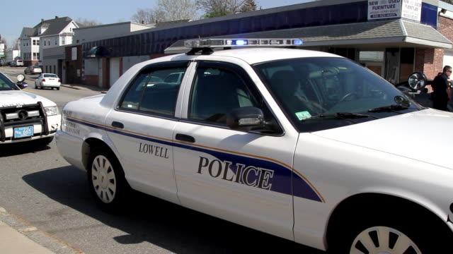 MS Lowell police squad car with flashing lights parked at