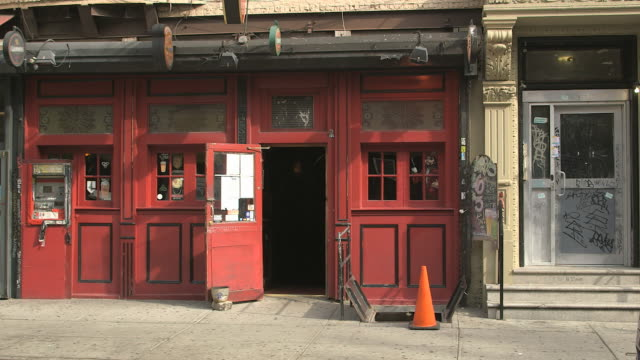 stockvideo's en b-roll-footage met cu lower east side downtown manhattan dive bar pub with red painted faã§ade and nearby graffiti - signage removed/ new york, new york, usa - bar gebouw